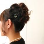【結婚式ヘア】黒いドレスに合う黒い花飾りのアップスタイルヘア